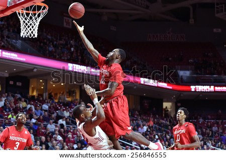 PHILADELPHIA - FEBRUARY 26: Houston guard Jherrod Stiggers (21) crashes into Temple guard Will Cummings (2) drawing a charge during the AAC college basketball game  February 26, 2015 in Philadelphia.  - stock photo