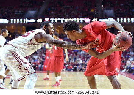 PHILADELPHIA - FEBRUARY 26: Temple Owls forward Jaylen Bond (15) reaches in to guard a Houston defender during the AAC conference college basketball game  February 26, 2015 in Philadelphia.  - stock photo