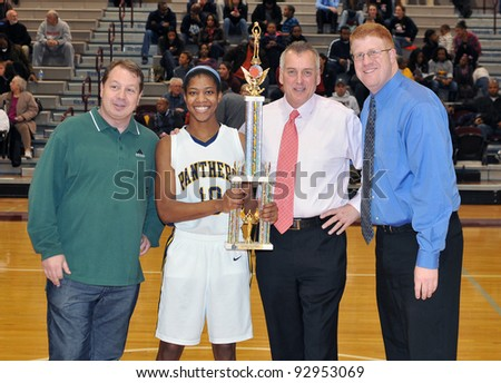PHILADELPHIA - JANUARY 14: Cheltenham's Ciara Andrews (#10) accepts a game MVP award from Jeremy Treatman (green) & Don Tollefson (white) at the Play by Play Classic January 14, 2012 in Philadelphia - stock photo