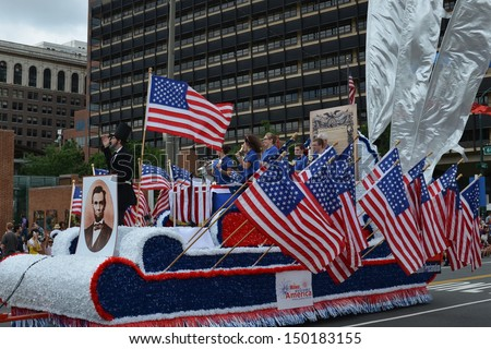 PHILADELPHIA- JULY 4: Abraham Lincoln rides a float in the Independence Day Parade as it makes its way along Market St. on July 4, 2013 in Philadelphia, PA. - stock photo