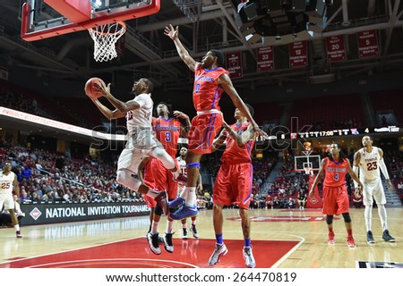 PHILADELPHIA - MARCH 25: Temple Owls guard Will Cummings (2) makes contact as he goes up for a shot during the NIT quarterfinal basketball game March 25, 2015 in Philadelphia. - stock photo