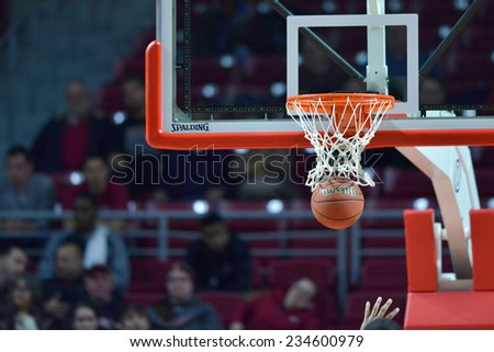 PHILADELPHIA - NOVEMBER 25: A basketball falls through the hoop for a score during the Big 5 basketball game November 25, 2014 in Philadelphia.  - stock photo