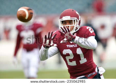 PHILADELPHIA - NOVEMBER 29:Temple Owls defensive back Alex Wells (21) prepares to catch a ball during pre game drills November 29, 2014 in Philadelphia. - stock photo