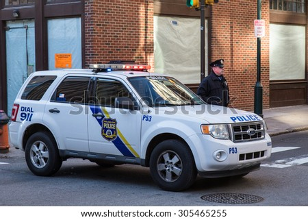 PHILADELPHIA, PA - JANUARY 1, 2015: A uniformed Philadelphia Police officer stands beside a police vehicle. - stock photo