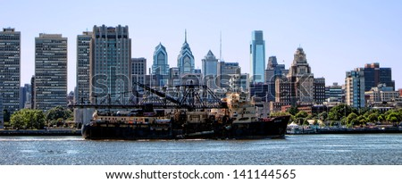 PHILADELPHIA, PA, JUNE 4 - Trailing hopper dredge vessel McFarland dredging ship sailing on the Delaware River by Center City Philadelphia in Pennsylvania on June 4, 2013 in Philadelphia Pennsylvania - stock photo