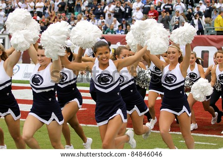 PHILADELPHIA, PA. - SEPTEMBER 17: Penn State cheerleaders run onto the field prior to a game against Temple on September 17, 2011 at Lincoln Financial Field in Philadelphia, PA. - stock photo
