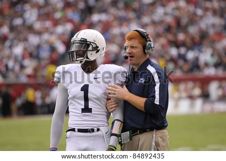 PHILADELPHIA, PA. - SEPTEMBER 17: Penn State Quarterback back Robert Bolden talks strategy with Coach McQueary against Temple on September 17, 2011 at Lincoln Financial Field in Philadelphia, PA. - stock photo