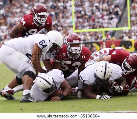 PHILADELPHIA, PA. - SEPTEMBER 17: Penn State running back Brandon Beachum (No 3) is at the bottom of pile of players against Temple on September 17, 2011 at Lincoln Financial Field in Philadelphia, PA. - stock photo