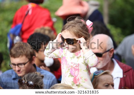 PHILADELPHIA, PA - SEPTEMBER 26 2015: Pope Francis celebrated mass at the Cathedral Basilica of Peter & Paul in downtown Philadelphia. Little girl tries on sunglasses - stock photo