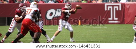 PHILADELPHIA, PA. - SEPTEMBER 8: Temple quarterback Chris Coyer looks for a receiver against Maryland on September 8, 2012 at Lincoln Financial Field in Philadelphia, PA.  - stock photo