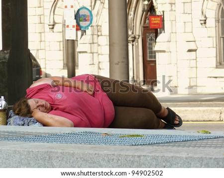 PHILADELPHIA, PENNSYLVANIA, USA - SEPTEMBER 5: Unidentified woman sleeps on sidewalk on September 5, 2011 in Philadelphia. A recent survey found more than 500 homeless people living in Philadelphia. - stock photo