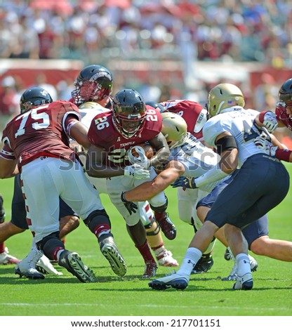 PHILADELPHIA - SEPTEMBER 6: Temple Owls running back Jamie Gilmore #26tries to squeeze through a gap in the line during a NCAA football game between Temple and Navy September 6, 2014 in Philadelphia.  - stock photo