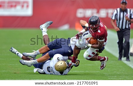 PHILADELPHIA - SEPTEMBER 6: Temple Owls running back Kenneth Harper #4 is tackled near the sidelines in a NCAA football game between Temple and Navy September 6, 2014 in Philadelphia.