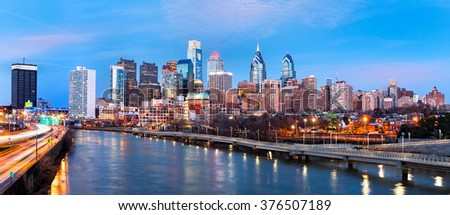 Philadelphia skyline panorama at dusk. Schuylkill expressway traffic runs parallel to Schuylkill river.