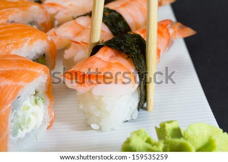 Philadelphia sushi roll with shrimp sushi nigiri in chopsticks with ginger and wasabi on white plate