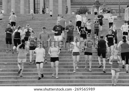"""PHILADELPHIA, USA - JUNE 11, 2013: People run down famous Rocky Steps in Philadelphia. The steps were made famous by the film """"Rocky"""" and are known among runners of the world. - stock photo"""