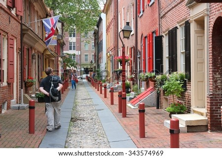 PHILADELPHIA, USA - JUNE 11, 2013: People visit Elfreth's Alley in Philadelphia. The alley is a National Historic Landmark. It dates back to 1702. - stock photo