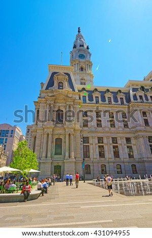 Philadelphia, USA - May 4, 2015: Philadelphia City Hall with fountain on Penn Square. Tourists on the square. Pennsylvania, USA. With special sun flare - stock photo