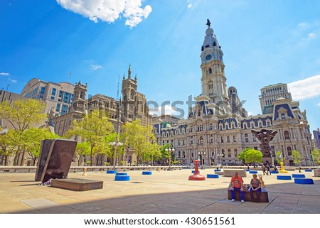 Philadelphia, USA - May 4, 2015: Square at Philadelphia City Hall with sculptures such as Government of the people sculpture. Tourists on the square. Philadelphia City Hall and Church on background