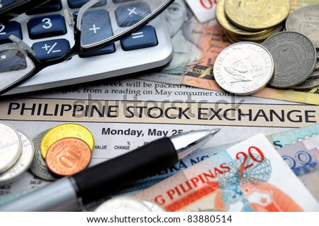 Philippine money, calculator, glasses an d ball point on top of a stock market report
