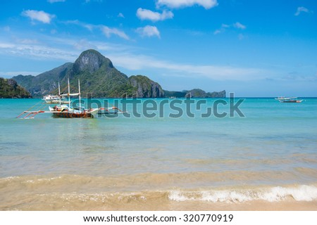 Philippines fishing boat in clear sea water and rocky island on the background in El Nido, Palawan