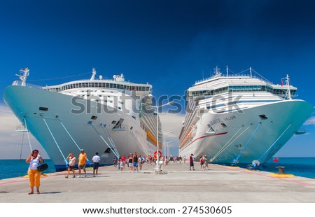 "PHILIPSBURG, SAINT MARTIN - 10:00 AM. AUGUST 23, 2007: Giant cruise ships Carnival ""Valor"" and ""Mariner of the Seas"" are docked together. Over 7,000 passengers are coming out to visit Caribbean island - stock photo"