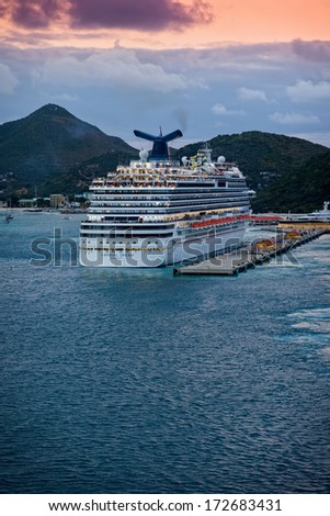 PHILIPSBURG, ST. MAARTEN - JAN. 16, 2013:  The Carnival Dream, Carnival Cruise Line's largest ship, departs from the Caribbean island of St. Maarten, a popular travel destination. - stock photo
