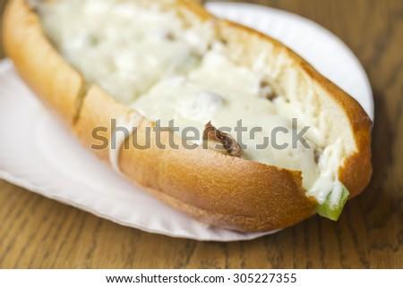 Philly Cheesesteak loaded with mozzarella cheese on submarine bun - stock photo