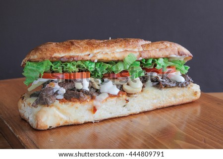 Philly sandwich filled with meat and veggies - stock photo