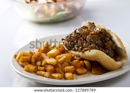Philly Steak Sandwich with fried potatoes and salad in the background - stock photo