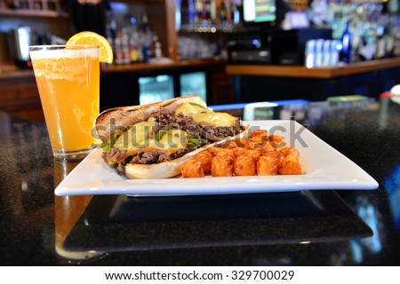 Philly steak sandwich with potato puffs - shredded steak smothered with sauteed mushrooms, sauteed onions, sauteed green peppers, and Gouda cheese on a hoagie bun - stock photo