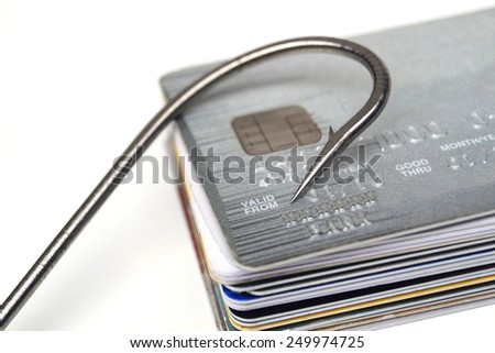 Phishing - A big fish hook on a pile of credit cards - stock photo