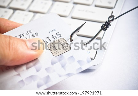 phishing - fish hook with a credit card on white computer keyboard - stock photo