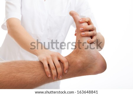 Phisiotherapist making a foot rehabilitation in physiotherapy clinic - stock photo