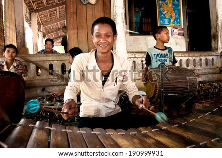 PHNOM PENH, CAMBODIA - DEC 28: Unidentified local child plays in traditional gamelan instruments outside Angkor Wat on December 28, 2010 in Phnom Penh, Cambodia. - stock photo