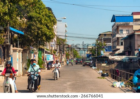 PHNOM PENH, CAMBODIA - FEBRUARY 28, 2014: Motorbikes and other traffic make their way along a street by a canal in the Cambodian capital. Modern skyscrapers are visible in the distance. - stock photo