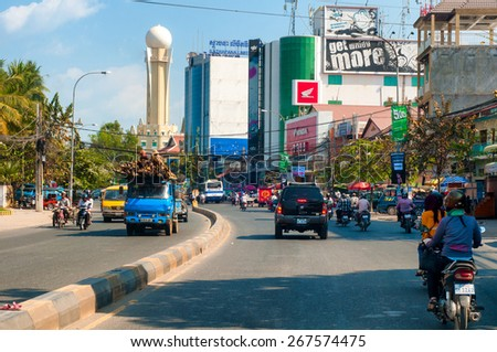 PHNOM PENH, CAMBODIA - FEBRUARY 28, 2014: Traffic makes its way along Preah Monivong Boulevard in the crowded Cambodian capital, past modern high rises and thriving commerce. - stock photo