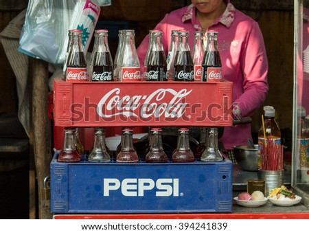 Phnom Penh, Cambodia- January 02, 2014. Coca-Cola and  Pepsi bottles stacked in plastic container - vintage style. Symbolic representation of one of the greatest business rivalries of all time.
