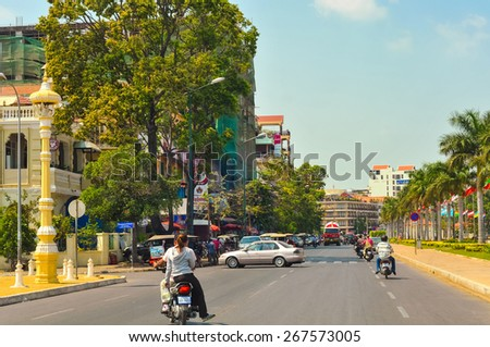 PHNOM PENH, CAMBODIA - MARCH 1, 2014: Motorbikes and other traffic move along Preah Sisowath Quay, the swankiest section of the Cambodian capital, with upscale stores, restaurants, and hotels. - stock photo