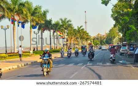 PHNOM PENH, CAMBODIA - MARCH 1, 2014: Traffic moves along Preah Sisowath Quay along the Tonle Sap riverfront with its parade of palms and international flags, heading toward Royal Palace Park. - stock photo