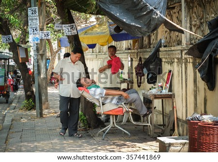 PHNOM PENH, CAMBODIA : Traditional lifestyle of people in Cambodia, Barber work at open air shop on pavement, man cut hair for senior to make living on March 17, 2015 - stock photo