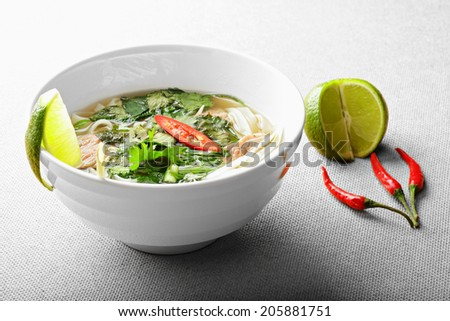 Pho bo soup with lime and chili over the gray surface - stock photo
