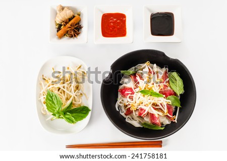 Pho - Vietnamese Rare Beef noodle soup on white background with Hoisin Sauce, Hot sauce, spices, beansprouts, and fresh basil - stock photo