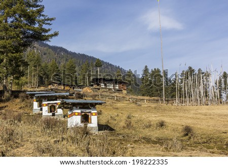 PHOBJIKA VALLEEY, BHUTAN - MARCH 4, 2014: A farmers house and a few choertens (chortens, stupas) in the beautiful Phobjikha valley, Bhutan, at a height of 3000m. At the side are some prayer flags.