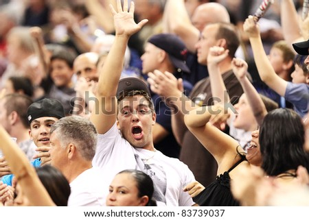 PHOENIX, AZ - APRIL 2: Excited Arizona Rattlers fans cheer during Arena Football League action against the Orlando Predators at U.S. Airways Center on April 2, 2011 in Phoenix AZ. - stock photo