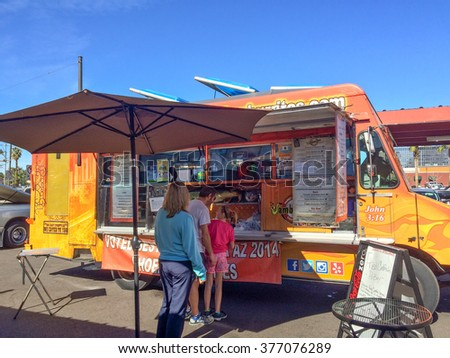 PHOENIX, AZ - FEBRUARY 5, 2016: A family of three ordering lunch from Jamburritos Express Food Truck at designated outdoor spot in downtown of Phoenix, AZ - stock photo