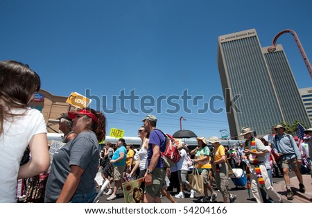 PHOENIX, AZ - MAY 29: Crowd passing in front of light rail during Arizona anti SB1070 march  May 29, 2010 in Phoenix, AZ. - stock photo