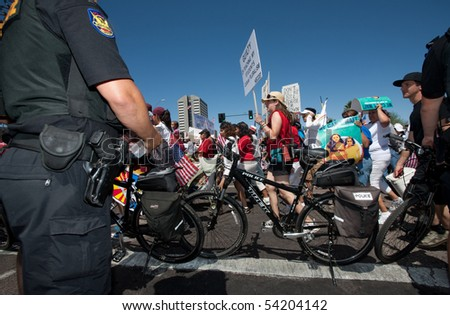 PHOENIX, AZ - MAY 29:  Police observing Arizona anti SB1070 march. May 29, 2010 in Phoenix, AZ. - stock photo