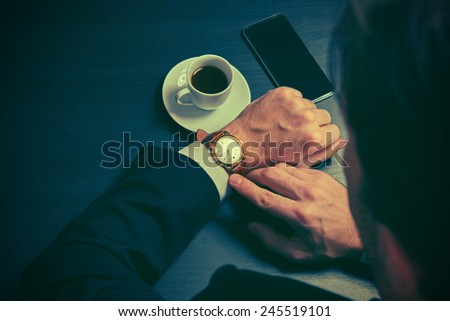 phone and a cup of coffee in the hands of a businessman. stylish business still life in dark colors - stock photo
