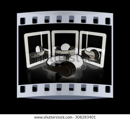 phone and headphones on a black background. The film strip - stock photo